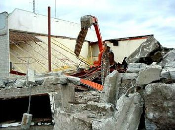 Excavator in rubble wall and building frame